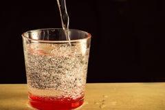 Un vidrio de agua con las burbujas y salpica Foto de archivo libre de regalías