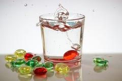 Un vidrio de agua con las burbujas y salpica Fotos de archivo libres de regalías