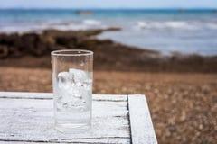 Un vidrio de agua con los cubos de hielo en la tabla de madera blanca en la playa fotografía de archivo libre de regalías