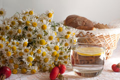 Un vidrio de agua con una rebanada del limón en ella, un ramo de manzanillas y una placa de ciruelos maduros en una superficie de Imágenes de archivo libres de regalías
