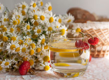 Un vidrio de agua con una rebanada del limón en ella y un ramo de manzanillas en una superficie del cordón adornada con las cader Fotografía de archivo libre de regalías