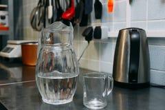 Un vidrio de agua dulce con el crafin en el fondo de una cocina moderna fotografía de archivo