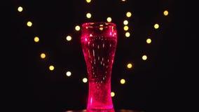 Un vidrio de agua en luz multicolora está haciendo girar, cóctel es color de los cambios Concepto de la barra almacen de video