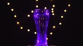 Un vidrio de agua en luz multicolora está haciendo girar, color de los cambios del cóctel rápidamente Concepto de la barra metrajes