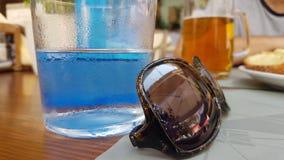 Un vidrio de agua fría y de gafas de sol imagen de archivo
