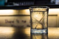 Un vidrio de agua potable fría en la tabla Fotos de archivo
