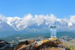 Un vidrio de agua pura en un fondo de montañas nevosas Fotos de archivo libres de regalías