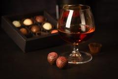 Un vidrio de brandy fuerte de la bebida alcohólica o brandy y caramelo hecho del chocolate belga en un fondo oscuro imagen de archivo