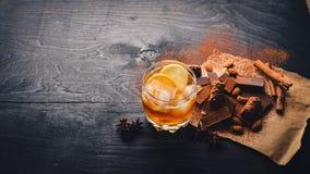 Un vidrio de brandy whisky Surtido de chocolates Fotos de archivo