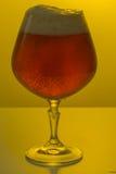 Un vidrio de cerveza en fondo coloreado imagenes de archivo