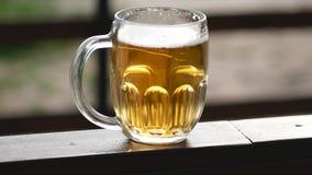 Un vidrio de cerveza en la tabla panorámica almacen de video