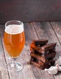 Un vidrio de cerveza ligera y de tostadas aromáticas calientes fritas del ajo del bl Imagen de archivo