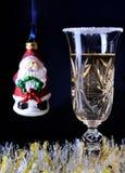 Un vidrio de champán con pequeño Santa Imagen de archivo libre de regalías