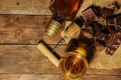Un vidrio de coñac o de whisky en una tabla rústica con el chocolate Imagenes de archivo