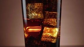 Un vidrio de cola de restauración con los cubos de hielo flotantes metrajes