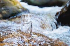 Un vidrio de cristal con el agua potable de la montaña pura se opone en una roca en el curso de un río de la montaña al contexto Imagen de archivo