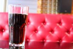 Un vidrio de cristal con soda marrón, dulce, fría, sabrosa, de restauración en la tabla en un café por la tarde contra fotografía de archivo libre de regalías