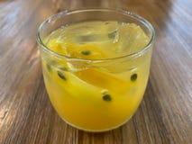 Un vidrio de fondo del jugo de la fruta de la pasión imagen de archivo
