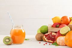 Un vidrio de jugo con una paja de diversas frutas imagen de archivo