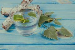Un vidrio de jugo del abedul en fondo de madera Foto de archivo