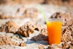 Un vidrio de jugo en la playa Foto de archivo
