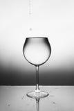 Un vidrio de líquido claro y de una gota que baja en ella Fotografía de archivo