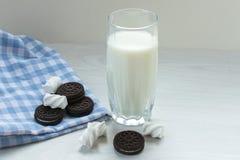Un vidrio de leche con galletas de microprocesador de chocolate y una marcha del melow en una tabla blanca imagen de archivo libre de regalías