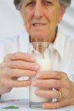 Un vidrio de leche es guardado por una mujer mayor entre 70 y 80 años Imagen de archivo libre de regalías