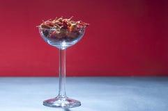 Un vidrio de licor con las pimientas rojas en él foto de archivo