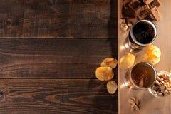 Un vidrio de luz y un vidrio de cerveza oscura y de bocados en una tabla marrón de madera con un lugar para la inscripción imagen de archivo libre de regalías