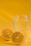 Un vidrio de soda y dos tajó naranjas Fotos de archivo