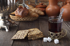 Un vidrio de té con la galleta y los bollos cerca del samovar Foto estilizada retra Imagen de archivo