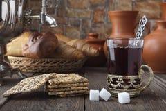 Un vidrio de té con una galleta y los rollos cerca del samovar y de platos de cerámica en una tabla vieja Foto estilizada retra Imagen de archivo libre de regalías