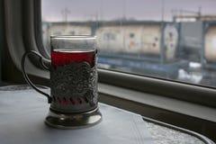 Un vidrio de té en la tabla en el compartimiento del tren, fuera de los trenes de la ventana fotos de archivo libres de regalías