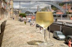 Un vidrio de vino blanco con el puente en el fondo imagenes de archivo