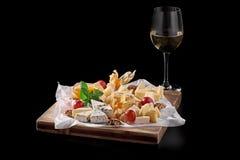 Un vidrio de vino blanco y una variedad de quesos, de nueces y de frutas secadas en un fondo negro café, pub-menú, el concepto fotos de archivo libres de regalías