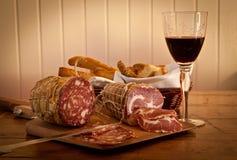 Un vidrio de vino con el salami y el pan hecho en casa. fotos de archivo