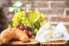 Un vidrio de vino con las uvas, el queso y el cruasán rojos y verdes Imagen de archivo libre de regalías