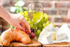 Un vidrio de vino con las uvas, el queso y el cruasán rojos y verdes Fotografía de archivo