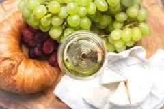 Un vidrio de vino con las uvas, el queso y el cruasán rojos y verdes Imágenes de archivo libres de regalías