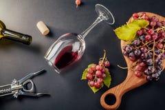 Un vidrio de vino con una botella, un sacacorchos y uvas Foto de archivo