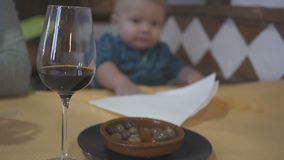 Un vidrio de vino contra la perspectiva de un niño de un año El concepto de una familia y de un alcoholismo disfuncionales metrajes