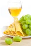 Un vidrio de vino, de queso y de uvas en la madera Fotos de archivo