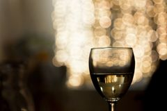 Un vidrio de vino en un fondo encendido Foto de archivo libre de regalías