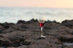 Un vidrio de vino en la playa Imagenes de archivo