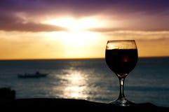Un vidrio de vino en la puesta del sol imagenes de archivo