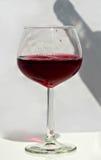 Un vidrio de vino rojo con la sombra de la botella Imagen de archivo libre de regalías