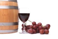 Un vidrio de vino rojo con las uvas y el barril. Fotografía de archivo libre de regalías