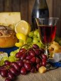 Un vidrio de vino rojo con queso y uvas en la tabla Imagen de archivo