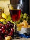 Un vidrio de vino rojo con queso y uvas en la tabla Imagen de archivo libre de regalías